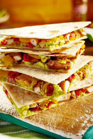 crispy: Close up of pork guacamole quesadillas on flat bread or wheat tortilla pieces in stack of four Stock Photo
