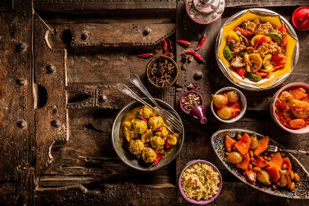 Erhöhte Ansicht der traditionelle Tajine Gerichte und frischen auf rustikalem Holztisch angeordnet Zutaten aus Old Door - Stillleben mit Textfreiraum Standard-Bild