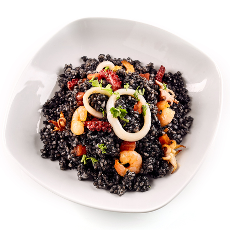 prepared dish: Close up first person perspective view of freshly prepared Arroz Negro garnished with various types of seafood in white dish