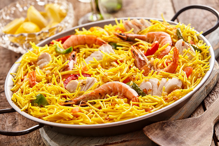 specialty: Multiple servings of yellow noodles and seafood specialty in metal pan with handles next to bowl over wooden table