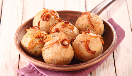 browned: Bowl of traditional kisse dumplings with browned fried onions served in a rustic bowl on a wooden table Stock Photo