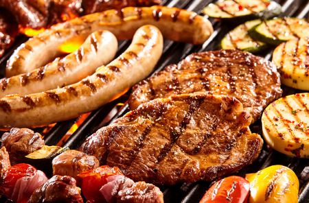 grilled: Hot dog sausages, beef steak, chicken patties and vegetables on hot flaming grill Stock Photo