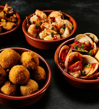 black fish: Traditional Spanish fried seafood and tapas appetizers in separate round bowls over black background Stock Photo