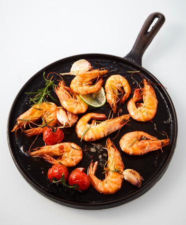 맛있는 구운 매운 새우 로즈마리, 신선한 마늘, 석 회와 체리 토마토 노련한 화이트 소박한 프라이팬에 오버 헤드에서 볼