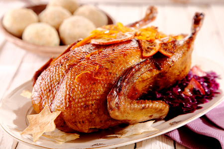 ducks: Single roasted chicken with star crackers on plate with cranberries and rolls in the background