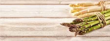 folate: Two bundles of raw green white asparagus tied with brown loose string over wooden plank background Stock Photo