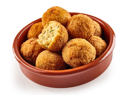 bacalao: Spanish bacalao croquettes made with salted dried codfish fried in breadcrumbs served for tapas in a small bow over white