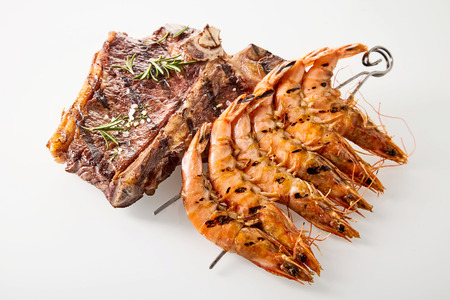 high angle view: Surf and turf marinated spicy T-bone beef steak and skewered queen prawns seasoned with rosemary, high angle view on white