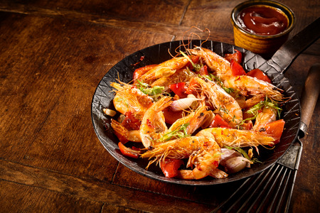 prawn: Spicy grilled or fried prawns with herbs, garlic and tomato served with a tomato ketchup or chili sauce on the side in a rustic pan, with copy space