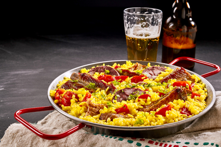 homo: Tasty traditional Spanish Al Homo paella with spare ribs and black pudding on saffron rice served in rustic bar for lunch with a pint of beer Stock Photo