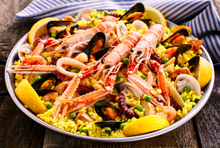 Close Up Overview of Colorful Spanish Seafood Paella Dish Served in Shallow Bowl with Blue and White Striped Linen Napkin on Rustic Wooden Table 版權商用圖片