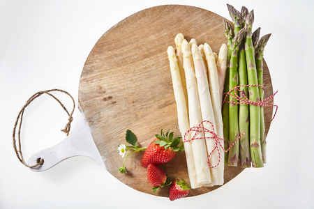bundled: Three ripe red strawberries with stem along side of bundled white and green asparagus on wooden tray Stock Photo