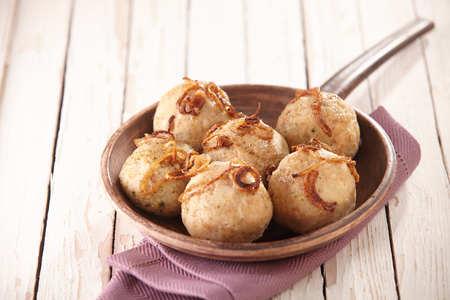 dumpling: Single pan full of German potato dumplings in the shape of balls over purple napkin over wooden surface