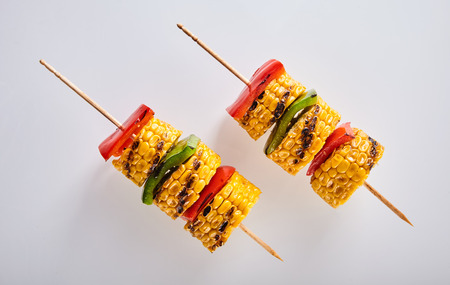 Delicious veggie skewers with corn and colorful red ad green bell peppers or capsicum for a healthy vegetarian accompaniment to a BBQ Banco de Imagens