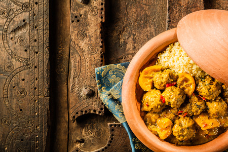 High Angle View of Traditional Tajine Berber Dish Made with Meatballs, Couscous and Savory Curry Sauce Served in Covered Clay Pottery Dish on Decorative Wooden Table with Napkin and Copy Space Stock Photo