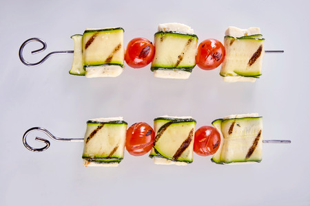 haloumi: Two healthy grilled haloumi cheese and tomato kebabs isolated on white viewed close up from above