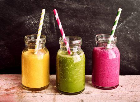 frutas tropicales: Vista lateral de perfil de saludables frutas y hortalizas que se sirven batidos en rústicas tarros de cristal con las pajas de beber rayadas coloridas en la tabla de madera con fondo oscuro