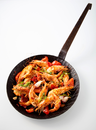 prawn: Gourmet grilled prawns in a spicy seafood appetizer seasoned with fresh herbs, garlic and red bell peppers and served in an old frying pan, high angle on white with copy space Stock Photo