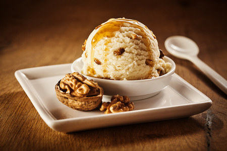 Delicious sweet vanilla ice cream dessert with coating of caramel syrup and whole cracked walnut beside it on square plate