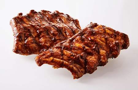 Two portions of delicious spicy marinated spare ribs barbecued over the grill over a white background Archivio Fotografico