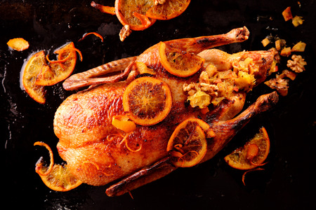 cooked: Top down view of one roasted whole chicken garnished with lemon fruit slices and stuffed on black background