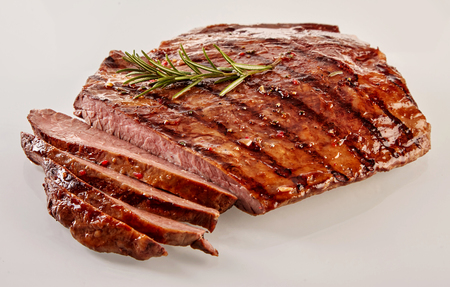 Carved barbecued medium-rare flank beef steak cut through to show the juicy texture garnished with a sprig of fresh rosemary, close up view over white