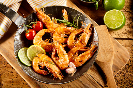 potherb: Delicious spicy grilled prawns with trimmings including fresh lime, garlic, cherry tomatoes and rosemary served in an old frying pan in a rustic country kitchen or restaurant