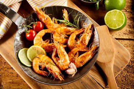 gamba: picantes deliciosas gambas a la plancha con guarniciones incluyendo limón fresco, ajo, tomates cherry y el romero servido en una vieja sartén en una cocina rústica o restaurante