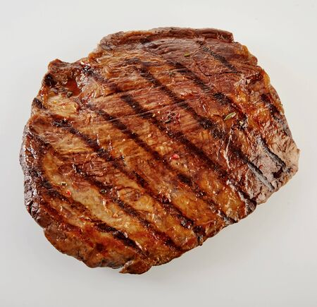 flank: Juicy thick medallion of lean flank beef steak marinated and grilled over a summer BBQ viewed close up from above over white Stock Photo