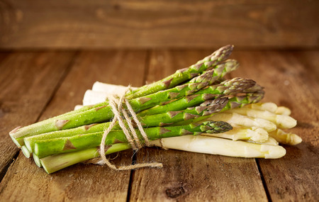 Bundles of white and green asparagus spears tied with string stacked on top of each other in wooden crate