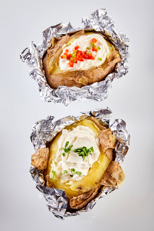 Two barbecued baked potatoes in tin foil topped with sour cream and garnished with chopped chives and peppers viewed from overhead still in the foil wrapping