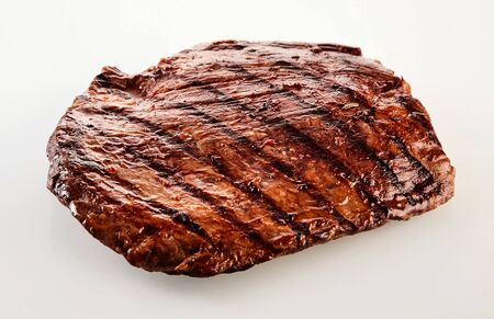 matured: Thick succulent portion of barbecued flank steak grilled in a spicy marinade viewed uncut over white at a high angle Stock Photo