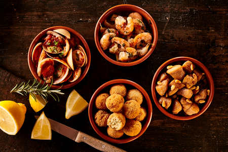 Four little Spanish style seafood appetizer bowls next to knife, rosemary sprigs and lemon slices over wooden table Stock Photo