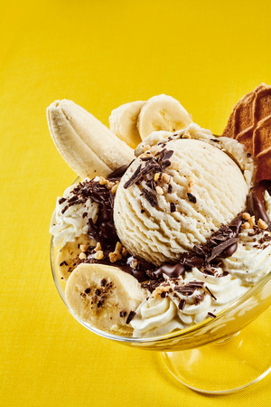 flaked: Delicious tropical banana summer dessert with diced fresh fruit served with ice cream and fresh cream garnished with flaked chocolate, yellow background high angle close up view
