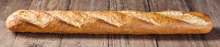 Bannière panoramique d'une baguette française mince croustillante fraîchement sorti du four sur une table en bois rustique Banque d'images