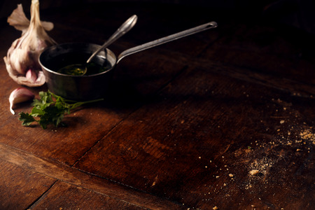 Background with cup of olive oil and garlic surrounding open area for copy space or other objects Stock Photo