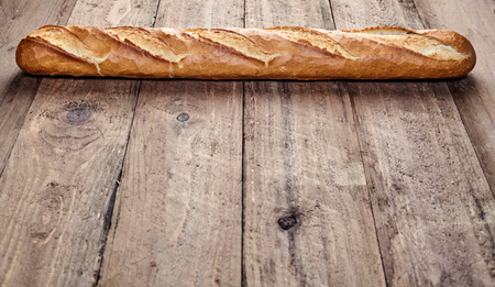 crust crusty: Freshly baked crusty French baguette forming a top border on rustic wooden boards with plenty of foreground copy space