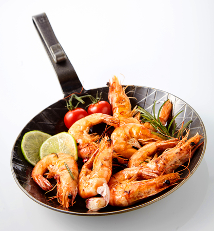 Delicious grilled spicy marinated queen prawns flavored with rosemary and served with slices of fresh lemon and tomatoes in a frying pan over white Stock Photo