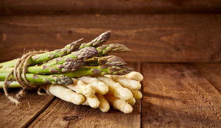 Two bunches of various green and white asparagus in horizontal format with many copy space on natural wooden background