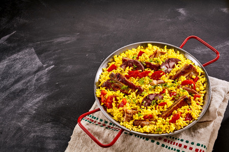 homo: Gourmet traditional Brazilian Al Homo paella with grilled spare ribs and black pudding in colorful yellow saffron rice seasoned with red peppers and herbs on a slate background with copy space
