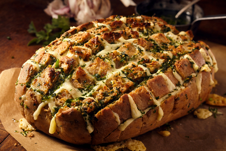 melted cheese: Delicious loaf of party bread stuffed with melted cheese and herbs on brown butcher paper over wooden table