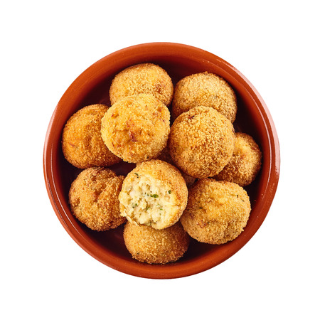 bacalao: Halved and whole fried bacalao croquettes served for Spanish tapas made with breaded dried codfish viewed from overhead on white