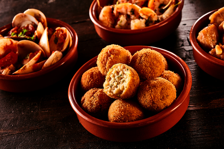 half ball: Bowl full of fried round croquettes with delicious stuffing beside other appetizers such as shrimp, clam and other seafood