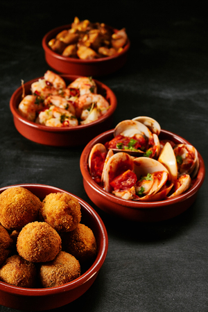 Four small red ceramic bowls full of Spanish fried croquette tapas, clams, shrimp and other ingredients Stock Photo