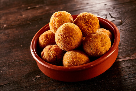 bacalao: Spanish bacalao croquettes made with dried salted codfish coated in breadcrumbs and fried, served in a small bowl for tapas