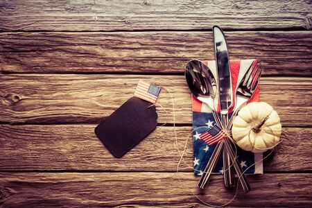 patriotic: Patriotic American autumn or fall place setting with a knife, spoon and fork on a Stars and Stripes napkin with a blank gift tag with an American flag, rustic wood background and vignette
