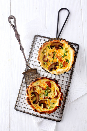 mini oven: Two tasty seasonal mushroom quiches made with a fresh autumn harvest of fungi, cheese and eggs seasoned with herbs, overhead view of two on a rack