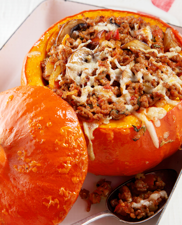 Delicious fall cuisine with a stuffed savory squash with spicy seasoned ground beef, cheese and herbs in the colorful orange hollowed out rind of a pumpkin
