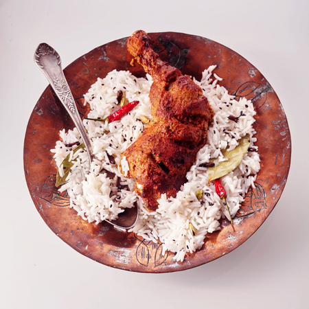 tandoori chicken: Overhead view of plate with savory indian dish of spicy chicken drumstick tandoori and herbed rice with silver spoon against a white background