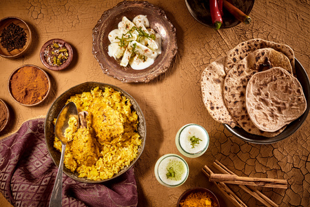 loamy: Top down view over table with Indian culinary dishes of curried chicken biryani with bread and sauces Stock Photo